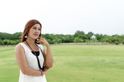 Attractive young redhead Asian woman. In trendy summer clothing posing in front of a green outdoors thinking with a friendly smile Royalty Free Stock Image