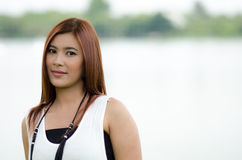 Attractive young redhead Asian woman. In trendy summer clothing posing in front of a lake outdoors looking at the camera with a friendly smile Royalty Free Stock Image