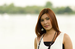 Attractive young redhead Asian woman. In trendy summer clothing posing in front of a lake outdoors looking at the camera with a friendly smile Stock Images