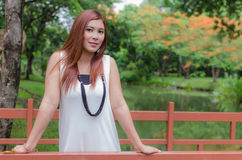 Attractive young redhead Asian woman. In trendy summer clothing posing in front of a lake outdoors looking at the camera with a friendly smile Stock Photo