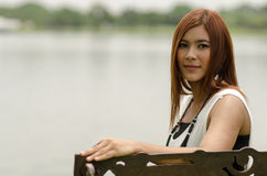 Attractive young redhead Asian woman. In trendy summer clothing sitting in front of a lake outdoors looking at the camera with a friendly smile Royalty Free Stock Photo