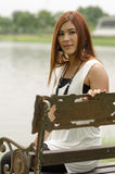 Attractive young redhead Asian woman. In trendy summer clothing sitting in front of a lake outdoors looking at the camera with a friendly smile Stock Image