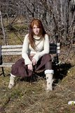 Attractive young redhead sitting on a bench. In the woods on a bright day Stock Images