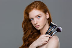 Attractive young redhead woman holding set of makeup brushes Stock Photos