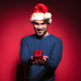 Attractive young santa giving you a small red gift. Smiling. On red background Royalty Free Stock Photography