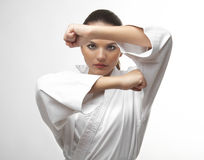 Attractive young sexy women in a karate pose. Attractive young sexy woman in a karate pose isolated on white Royalty Free Stock Photography