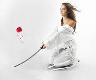 Attractive young sexy women with samurai sword. Attractive young sexy woman with samurai sword on white background Stock Photo