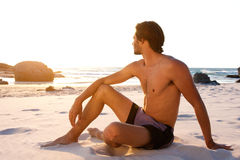 Attractive young shirtless man sitting on beach looking away. Portrait of attractive young shirtless man sitting on beach looking away Stock Images