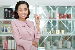 Asian Shop Assistant Posing for Photography. Attractive young shop assistant wearing pink blouse looking at camera with charming smile while standing against Royalty Free Stock Photos