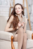 Attractive young slim brunette sitting in a big comfortable chair. Royalty Free Stock Photography