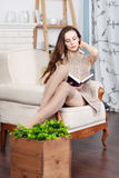 Attractive young slim brunette is sitting in a big comfortable chair. She is reading a book. Stock Image