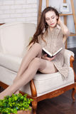 Attractive young slim brunette is sitting in a big comfortable chair. Royalty Free Stock Images