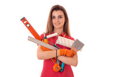 Attractive young slim builder girl makes renovations with tools in her hands isolated on white background Stock Photography
