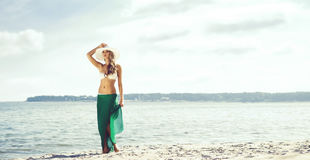 Attractive, young, slim woman wearing alluring swimwear and gree Stock Photography