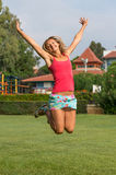 Attractive young smiling beautiful curly blonde hair slim girl fashion portrait in pink T-shirt  jumping in the field summer time Royalty Free Stock Photo