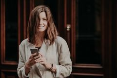 Attractive young smiling female blogger texts messages to followers, has recreation time, being in good mood, wears white fashiona royalty free stock photography