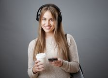 Attractive young smiling girl in headphones is holding a phone and a cup of coffee. Isolated on a gray background Royalty Free Stock Images