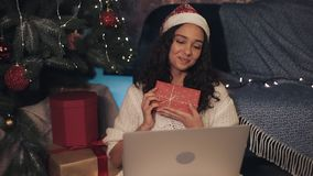 Attractive young smiling girl in santas hat having video call on her laptop sitting at home near Christmas tree. Woman stock video footage