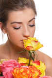 Attractive young smiling woman with flowers roses isolated Stock Photography