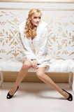 Attractive young smiling woman sitting at sofa Royalty Free Stock Photos