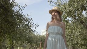 Attractive young smiling woman in straw hat and long white dress walking through the green summer garden. Carefree rural. Attractive young smiling woman in a stock footage