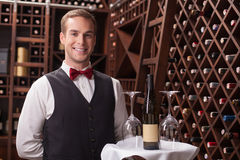Attractive young sommelier is working in. Handsome young waiter is serving a customer. He is carrying a tray with bottle of wine and wineglass. The man is Stock Photography
