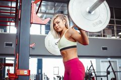 Girl squats with a barbell royalty free stock image