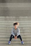 Attractive young sports woman sitting alone on steps Stock Photography