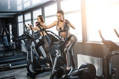 Attractive young sports woman is working out in gym. Doing cardio training on treadmill. Running on treadmill stock images