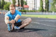 Attractive young sportsman is doing warming-up in Stock Photos