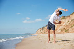 Attractive young sportsman standing and exercising on the beach Stock Photos