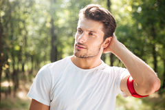 Attractive young sportsman standing in forest Royalty Free Stock Image