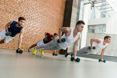 Attractive young sportsmen exercising with dumbbells Royalty Free Stock Images