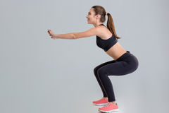 Attractive young sportswoman doing squats Royalty Free Stock Photos