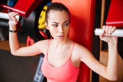 Attractive young sportswoman training arms muscles in gym Stock Photos