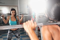 Back view portrait of a young woman doing squats with barbell at fitness gym royalty free stock photography