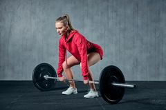 Attractive young sporty woman is working out in gym. Muscular woman is squatting with barbell royalty free stock photo