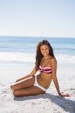 Attractive young tanned woman in bikini posing Stock Image