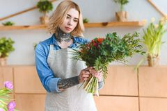 Attractive young tattooed woman in apron holding beautiful bouquet. In flower shop royalty free stock images