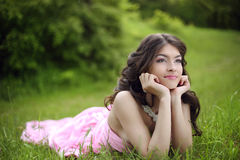 Attractive young teen girl with makeup wearing in pink dress lyi Stock Photos