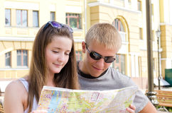 Attractive young tourist couple. Consulting a map as they go sightseeing in a foreign environment Stock Image