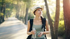 Attractive young tourist girl refreshing by drinking water after backpacker journey. In beautiful forest Royalty Free Stock Images
