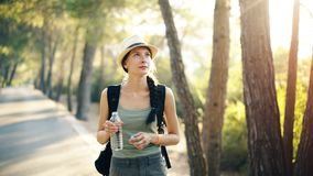 Attractive young tourist girl refreshing by drinking water after backpacker journey. In beautiful forest Stock Image