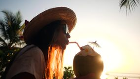 Attractive Young Tourist Hipster Girl Drinking Fresh Thai Coconut Water Coctail at Beach Against Beautiful Sunset. 4K