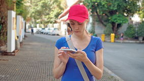 Attractive young tourist woman in red cap using online map in smartphone for the right directions stock video
