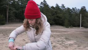 Attractive young tourist woman in a red hat collects a tourist tent near the forest on the coast. 4k stock video footage