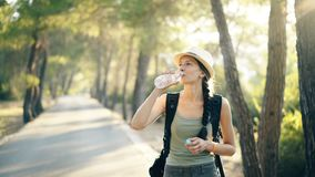 Attractive young touristy girl refreshing by drinkin water after backpacker journey stock footage