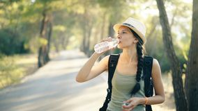 Attractive young touristy girl refreshing by drinkin water after backpacker journey stock video footage