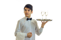 Attractive young waiter in a shirt raised in hand a tray with glasses Stock Images