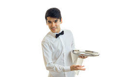 Attractive young waiter in a white shirt smiling leaning forward and holding a tray Stock Photo